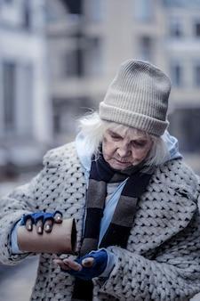 Jenseits der armut. traurige unglückliche frau, die auf der straße steht, während sie ihr geld überprüft