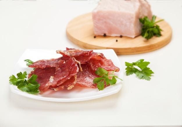 Jerky in einer tasse und rohem fleisch mit kräutern auf einem weißen teller.