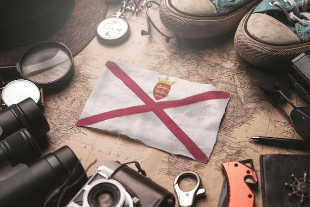 Jersey-flagge zwischen dem zubehör des reisenden auf alter weinlese-karte. touristisches bestimmungsort-konzept.
