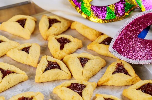Jerwish essen hamantaschen kekse mit marmelade, tallit und maske für purim.