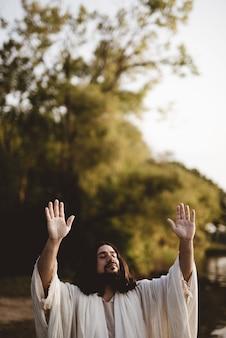 Jesus christus zeigt mit den händen zum himmel, während seine augen geschlossen sind