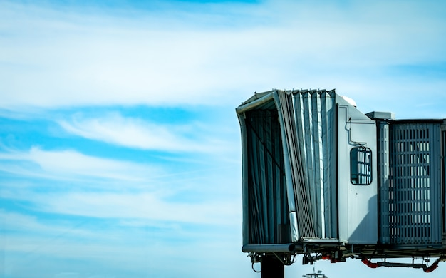 Jet bridge nach kommerzieller fluggesellschaft am flughafen gegen blauen himmel und weiße wolken abheben. flugzeugpassagier-einstiegsbrücke angedockt. leere düsenbrücke.