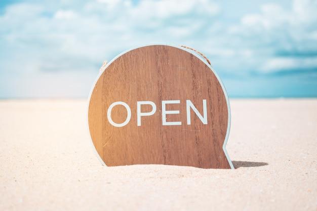 Jetzt offenes schild stehen auf sand sommer strand hintergrund metapher zu zeit zu reisen entspannen tourismus-saison mit copyspace.