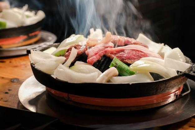 Jingisukan oder dschingis khan, japanisches gegrilltes hammelfleisch auf einer konvexen metallpfanne