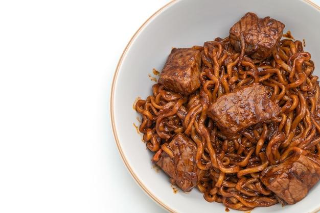 Jjapaguri oder chapaguri, koreanische schwarze bohnen würzige nudeln mit rindfleisch isoliert