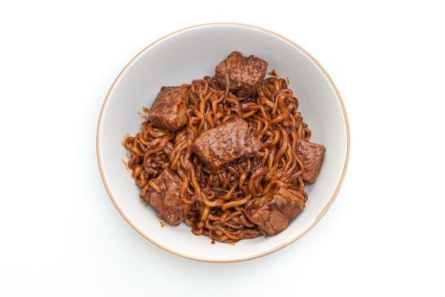 Jjapaguri oder chapaguri, koreanische schwarze bohnen würzige nudeln mit rindfleisch lokalisiert auf weißem hintergrund