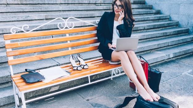 Job für unterwegs. außenbüro. erfolgreiche freiberuflerin, die am laptop-telefon auf der bank sitzt.