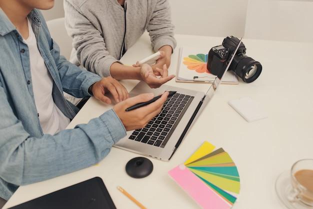 Job im kreativteam. junger geschäftsmann, der mit startup-projekt arbeitet, analysiert diagrammpläne und diskutiert im arbeitsplatzbüro, brainstorm-meeting-konzept
