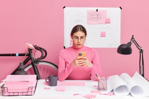 Job karriere beruf und berufskonzept. überraschte europäerin starrt auf smartphone-display-textnachrichten, die am bauprojekt arbeiten