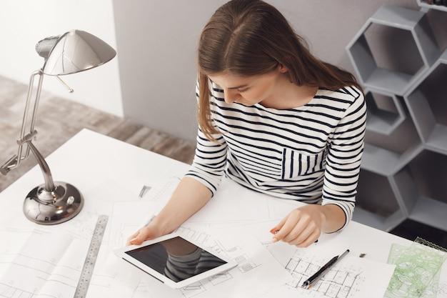 Job-, karriere- und geschäftskonzept. porträt des jungen modischen professionellen weiblichen designers, der am tisch sitzt, im digitalen tablettmonitor schaut, mit kunden plaudert, um einige details zu entscheiden.