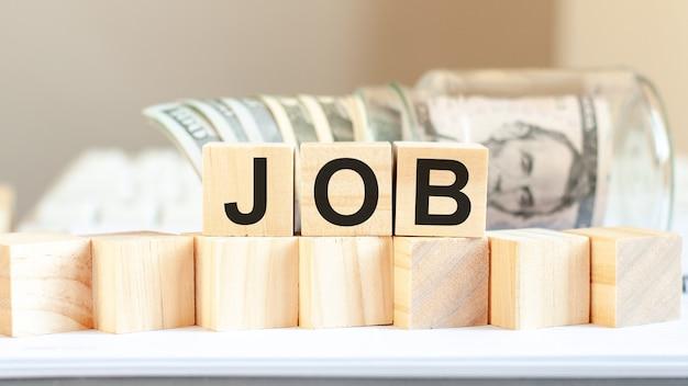 Jobwort geschrieben auf holzklötzen. amerikanische währung. geld- und finanzkonzept. bankkonzept.