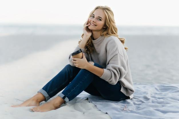 Jocund frau in den jeans, die am strand mit tasse kaffee sitzen. attraktive blinde frau, die im sand am herbsttag aufwirft.