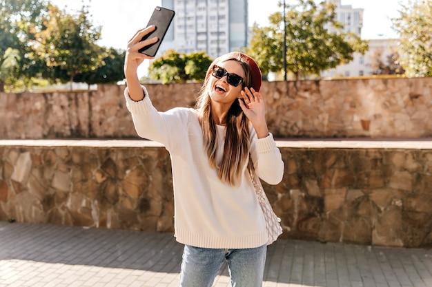 Jocund mädchen im weißen pullover macht selfie auf der straße. gut gekleidete frau in der baskenmütze, die spaß am guten herbsttag hat.
