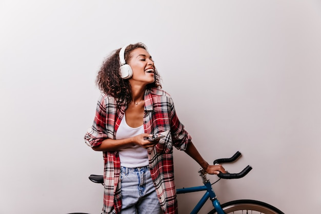 Jocund weibliches modell in den kopfhörern, die neben fahrrad stehen. innenaufnahme der reizenden lockigen frau im roten karierten hemd.