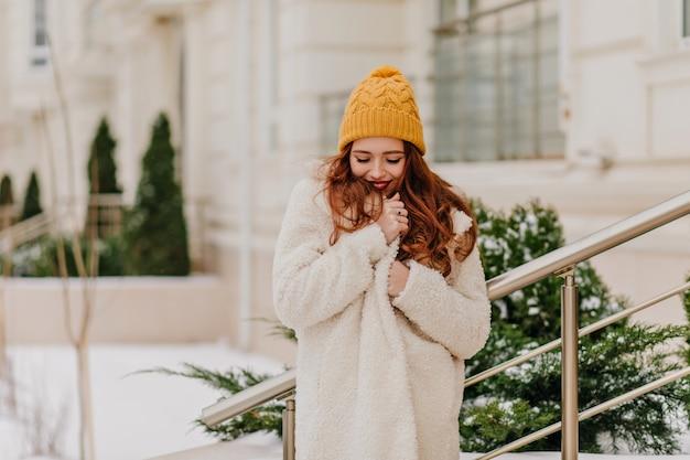 Jocund weißes mädchen, das im winter aufwirft. liebenswerte junge dame, die nahe grüner tanne steht.