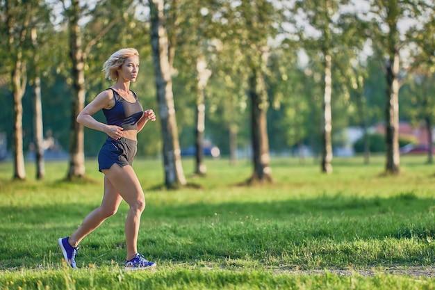 Joggen im park von schlanker frau in sportkleidung am sommertag