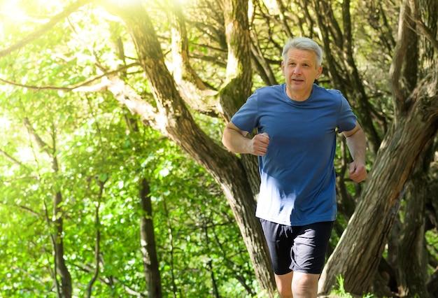 Joggen lebensstil - älterer attraktiver mann, der im sommerpark läuft