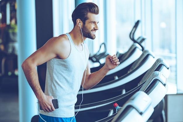 Joggen mit freude. seitenansicht eines jungen gutaussehenden mannes mit kopfhörern, der mit einem lächeln wegschaut, während er im fitnessstudio auf dem laufband läuft?