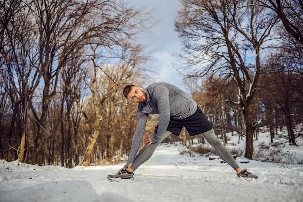 Jogger macht aufwärmübungen in der natur am verschneiten wintertag. wintersport, schneewetter, aufwärmübungen