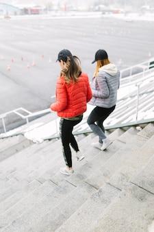 Jogger mit zwei frauen, der auf treppenhaus im winter läuft