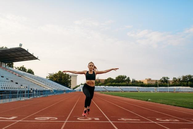 Joggerin in sportbekleidung überquert die ziellinie und trainiert im stadion. frau macht dehnübungen vor dem laufen auf der outdoor-arena