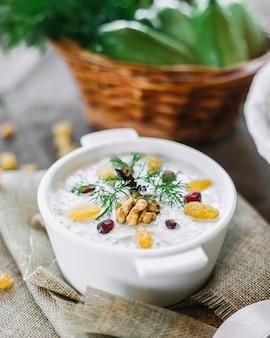 Joghurt aus der seitenansicht mit walnuss-rosinen und gemüse