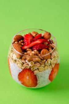 Joghurt chia pudding mit frischen erdbeeren, hafer und nüssen in einem glas auf grün