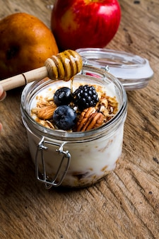 Joghurt des hohen winkels mit schwarzwald trägt nüsse und honig früchte