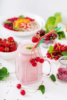Joghurt-erdbeer-smoothies in einem glas auf einem weißen tisch
