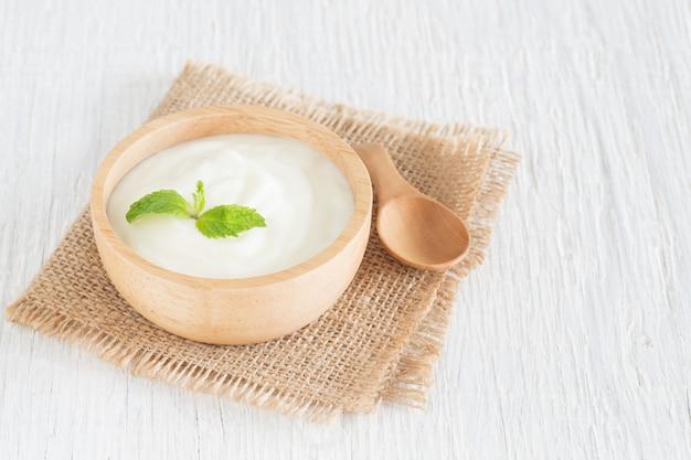 Joghurt in der holzschale auf weißem holztisch gesundes lebensmittelkonzept