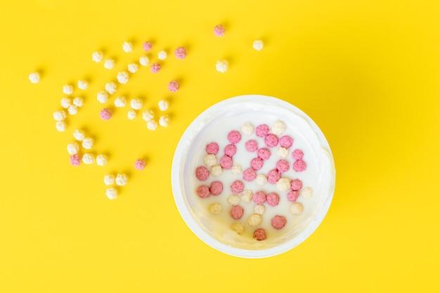 Joghurt in einem plastikbecher mit knusprigen flocken, müsli. draufsicht. morgen, frühstückskonzept.
