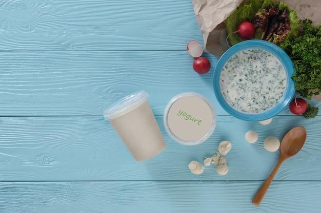Joghurt in einem plastikbehälter und grüns mit radieschen auf blauem holzhintergrund