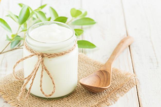 Joghurt in glasflaschen auf gesundem lebensmittelkonzept des weißen holztischs