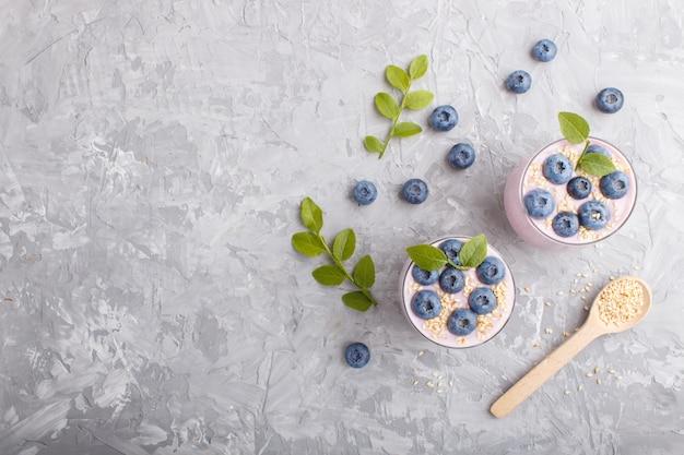 Joghurt mit blaubeere und indischem sesam in einem glas- und holzlöffel auf grauem konkretem hintergrund. ansicht von oben.