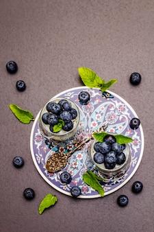 Joghurt mit blaubeeren und chiasamen auf schneidebrett