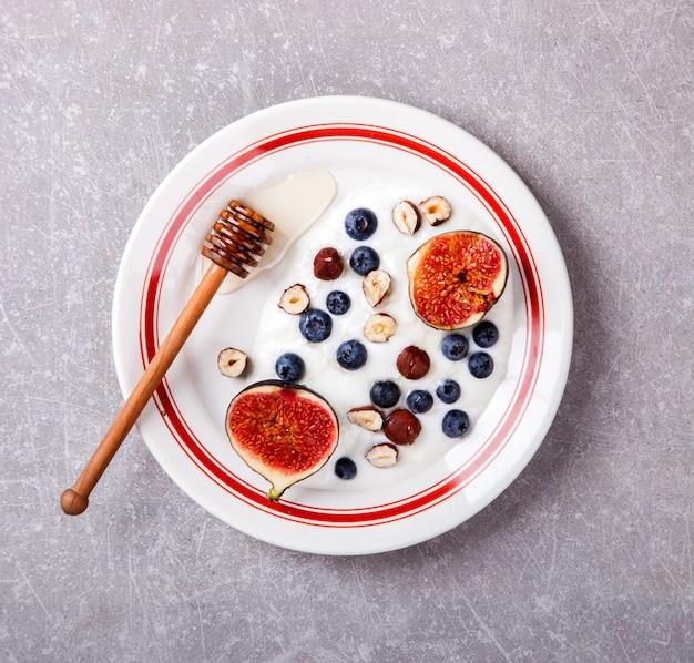 Joghurt mit frischen feigen, blaubeeren und honig aus beeren