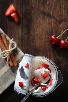 Joghurt mit frischen saftigen erdbeeren und kirschen auf einem holztisch