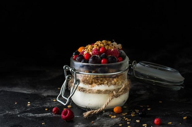 Joghurt mit gebackenem müsli und beeren im glas