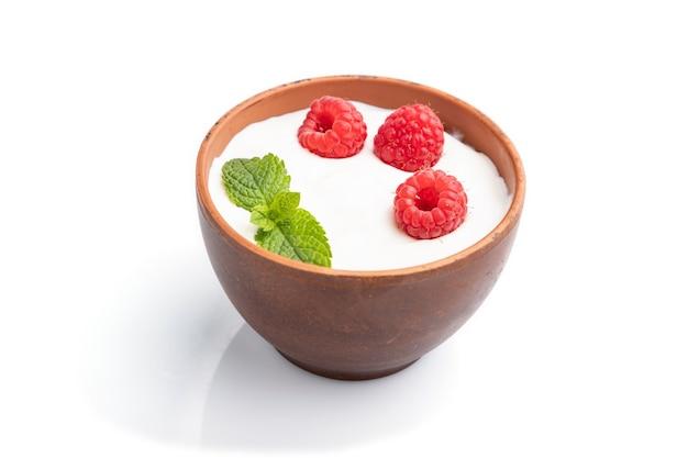 Joghurt mit himbeere im tonbecher lokalisiert auf weißem hintergrund. seitenansicht, nahaufnahme.