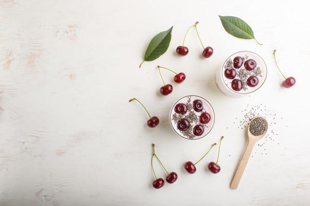 Joghurt mit kirschen, chiasamen und müsli im glas mit holzlöffel. draufsicht hintergrund