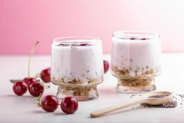 Joghurt mit kirschen, chiasamen und müsli im glas mit holzlöffel. seitenansicht.