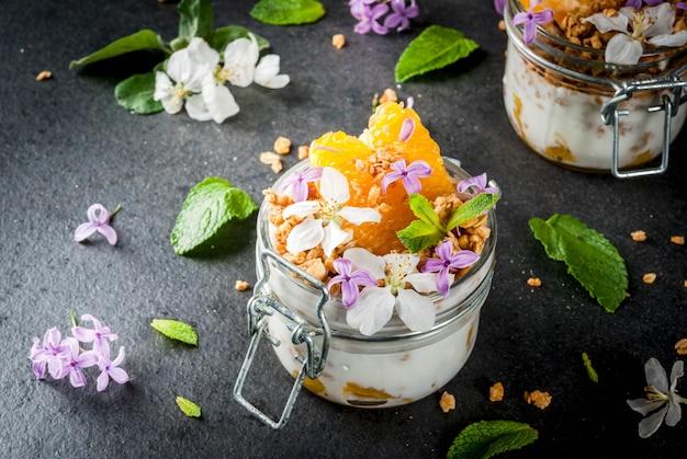Joghurt mit müsli, orange, minze und essbaren blüten