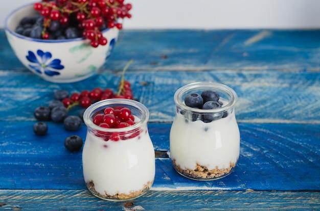 Joghurt mit roten beeren auf blauem hölzernem hintergrund.