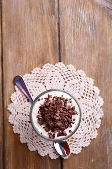 Joghurt mit schokoladencreme, gehackter schokolade und müsli, serviert in glas auf holzoberfläche