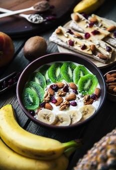 Joghurt mit verschiedenen früchten auf einem holztisch. nützliches essen, diät, bio.