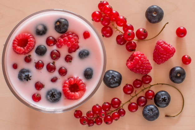 Joghurt mit waldbeeren auf holztisch