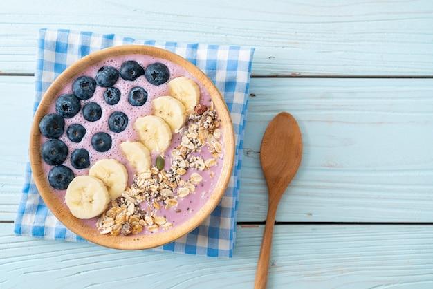 Joghurt oder joghurt-smoothie-schüssel mit blauen beeren, banane und müsli - gesunde ernährung
