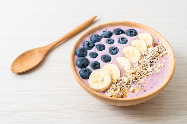 Joghurt oder joghurt-smoothie-schüssel mit blauen beeren, banane und müsli