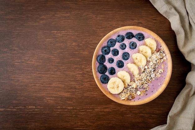 Joghurt oder joghurt-smoothie-schüssel mit blauen beeren, bananen und müsli - gesunde ernährung