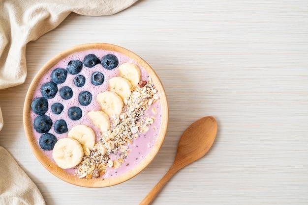 Joghurt oder joghurt-smoothie-schüssel mit blauen beeren, bananen und müsli